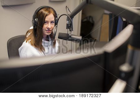 Portrait of young female host wearing headphones while communicating on microphone in radio studio