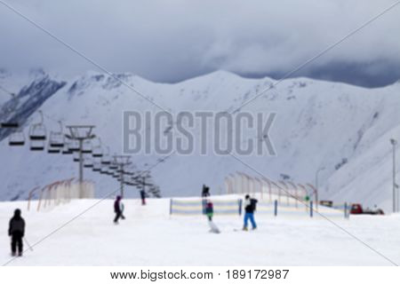 Blurred Ski Slope With Skiers And Snowboarders In Evening Not In Focus