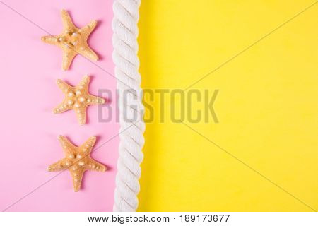 Three Starfishes And Sea Rope On Colored Backgrounds With Negative Space
