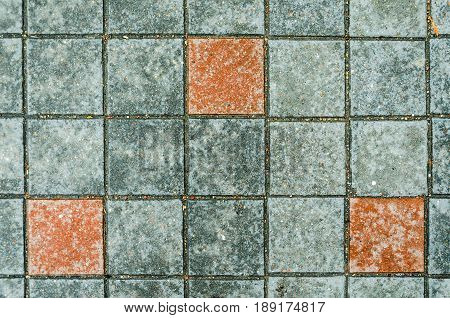 Gray concrete pavings on a sidewalk with red elements stones. Abstract background texture