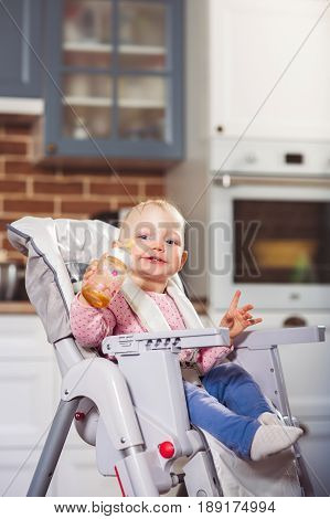 One year toddler girl sits on baby high chair with feeding bottle in her hand. Horizontal