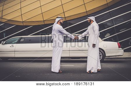 Arabic businessmen in Dubai handshaking with limousine in the background