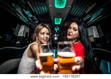 Pretty women having party in a limousine car
