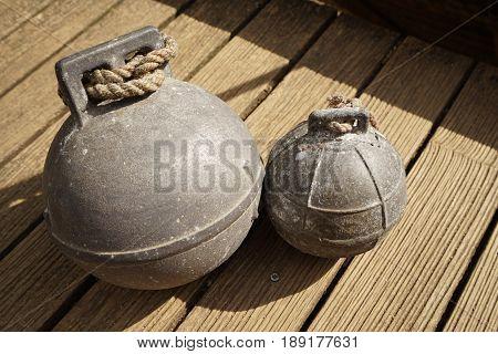 Two old fishing net metal balls on wooden floor