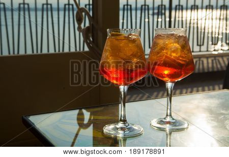 Waiter prepared the Aperol Sprits summer cocktail with Aperol prosecco ice cubes and orange in wine glass ready to drink on sunny terrace with sea view