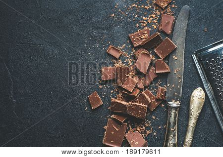 The Chunks Of Chocolate And Antique Knives Over Dark Concrete Background