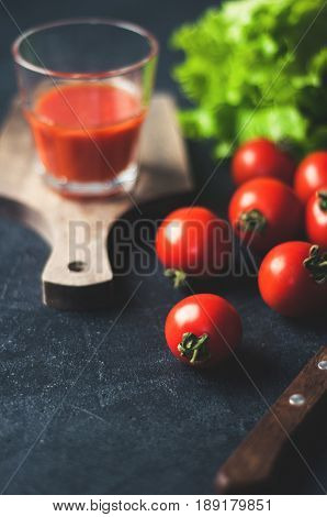 Fresh Tomatoes And Tomato Juice In Glass Over Dark Concrete Background