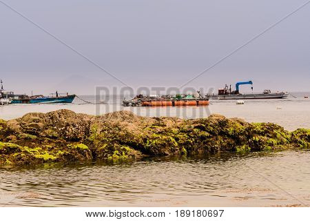 Seascape of large boulder covered with green algae with three fishing boats in the sea and a dull gray sky in the background.