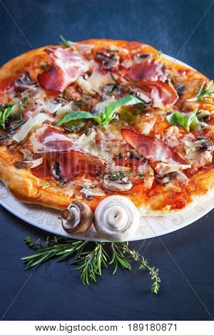 Pizza with Ham and Mushrooms on dark background