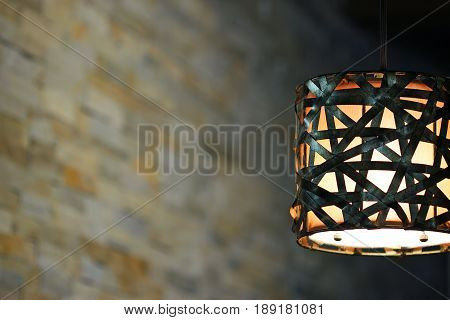 Modern light fixture illuminated in a home interior. Copy space.