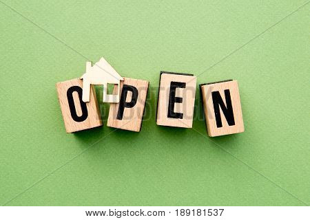 Open House - wooden block letters with home icon on green background