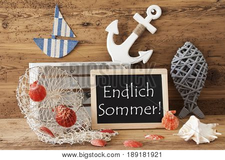 Blackboard With Nautical Summer Decoration And Wooden Background. German Text Endlich Sommer Means Hello Summer. Fish, Anchor, Shells And Fishnet For Maritime Contex.