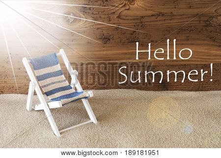 Sunny Summer Greeting Card With Sand And Aged Wooden Background. English Text Hello Summer. Deck Chair For Holiday Or Vacation Feeling.