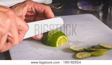 Bartender Cuts Green Lemons With A Ceramic Knife