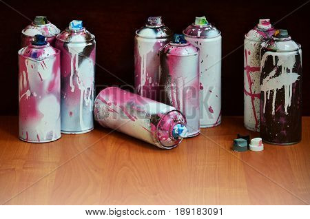 Still Life With A Large Number Of Used Colorful Spray Cans Of Aerosol Paint Lying On The Treated Woo