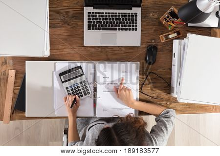High Angle View Of A Businesswoman Calculating Invoice On Office Desk