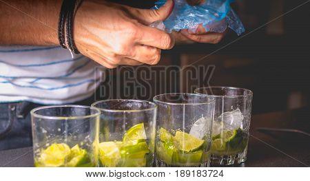 Bartender Puts Ice Cubes In Glasses Of Brezillian Caipirinha