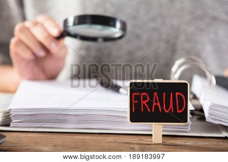Businesswoman Checking Documents With Fraud Board On Desk