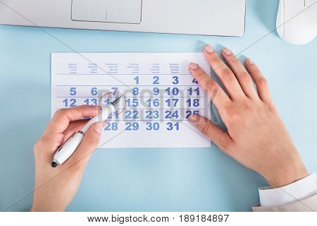 Close-up Of Businesswoman Drawing Circle On Calendar Date Over The Blue Desk
