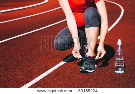 Pregnant sporty woman lacing sneakers on red running track of sport stadium. Concept of training workout exercising at summer outdoors. Sport healthy lifestyle while pregnancy.
