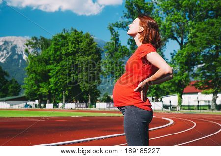 Pregnant sporty fitness woman suffering lower back pain on sport stadium. Concept of training workout exercising at summer outdoors. Sport healthy lifestyle while pregnancy.
