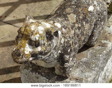 Weather-beaten statue of an animal against a sidewalk.