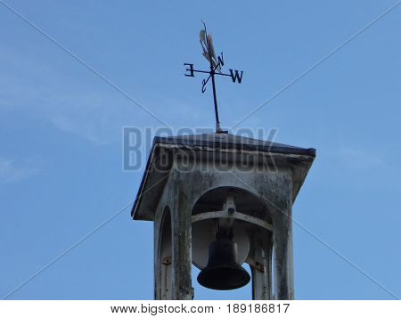 A weather-vane and bell against a crisp blue sky.