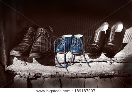 Beautiful cute nice shoes family. Father, mother black and white shoes boots and baby child blue color fashion shoes standing on old worn wood in village house. Vintage background texture. Baby shoes