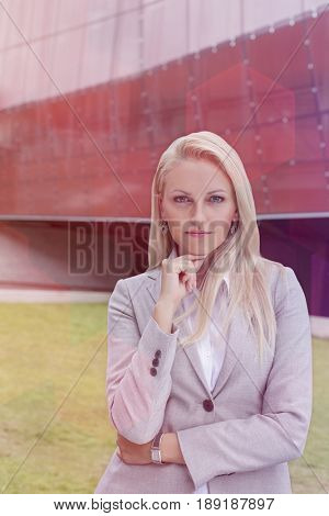 Portrait of confident businesswoman standing with hand on chin against office building