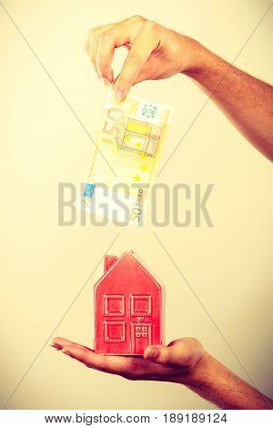 Man Putting Money Into House Piggybank