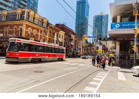 Toronto, Ontario, Canada, down town, May 20, 2017, great view of old street car with fragment of old and modern buildings, walking people in background