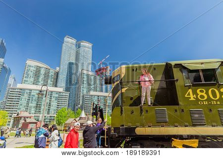 Toronto, Ontario, Canada, down town, May 20, 2017, nice amazing fragment view of old style retro diesel train with people getting on and exploring the train in down town district area on sunny day