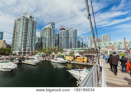 Toronto, Ontario, Canada, down town, May 20, 2017, beautiful amazing view of habourfront area with people walking on the bridge, yachts parked on water, various condo,office stylish modern buildings