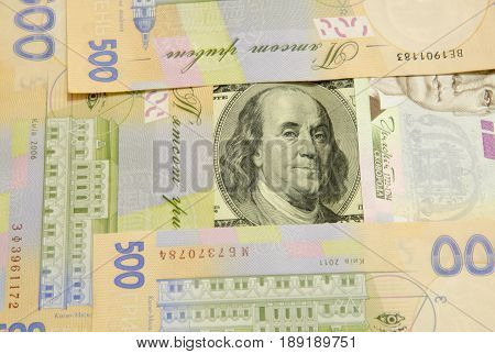 The denomination of one hundred dollars is surrounded by denominations of five hundred hryvnias.
