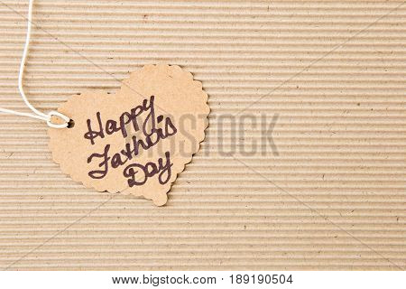 Happy Father's Day - on heart shape tag on corrugated cardboard background