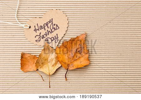 Happy Father's Day - on heart shape tag on corrugated cardboard background with autumn leaves