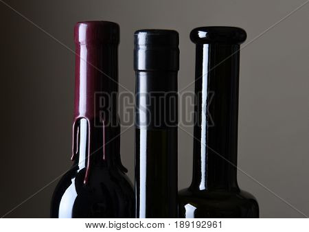 Closeup of three wine bottle necks against a light ot dark gray background.