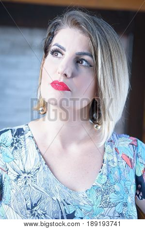Environmental portrait of beautiful and elegant blond woman on high key light with vivid red lipstick
