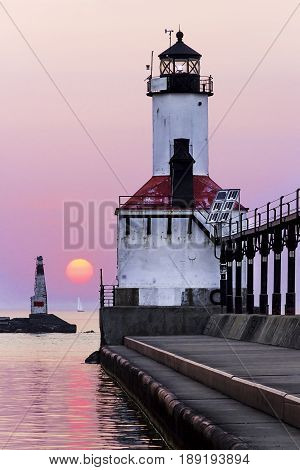 The East Pierhead Light in Michigan City Indiana with a sailboat on the horizon and setting sun.