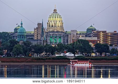 Harrisburg Pennsylvania skyline with State Capital Building and a river boat in the foreground. Tents are set up in the park for Memorial Day festivities. The view is from across the Susquehanna River.