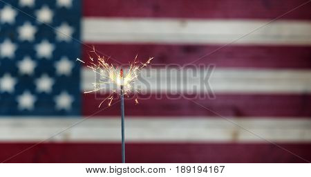 Burning sparkler with rustic wooden United States Flag in background