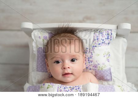 An overhead shot of a four month old alert baby girl. She is lying in a tiny bed and looking up at the camera.