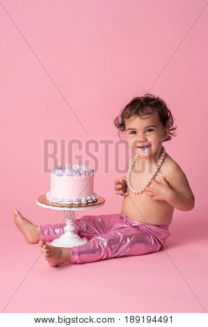 A happy one year old baby girl sitting with a cake. She is wearing pink leggings a string of pearls and has frosting on her chin.
