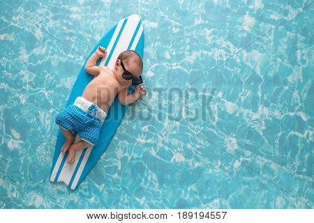 Two week old newborn baby boy sleeping on a tiny light blue and white surfboard. He is wearing light blue crocheted board shorts.