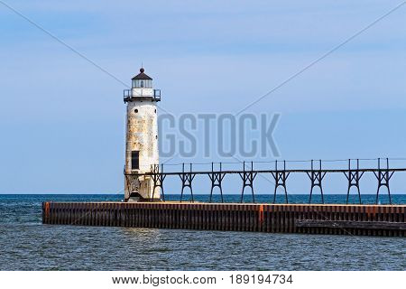 The Lighthouse at Manistee Michigan with its elevated catwalk approach is situated upon a breakwater that extends into Lake Michigan.