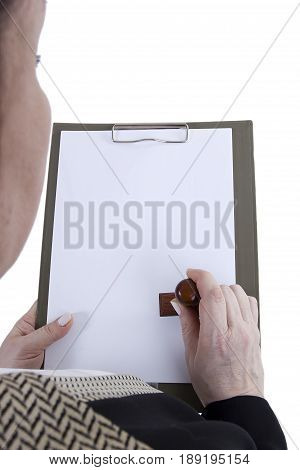 Hands with a sheet of paper and a stamp in the clipboard