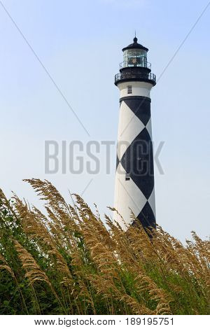 The Cape Lookout Lighthouse with its distinctive back and white diamond pattern stands on North Carolina's Southern Outer Banks with sea oats in the foreground.