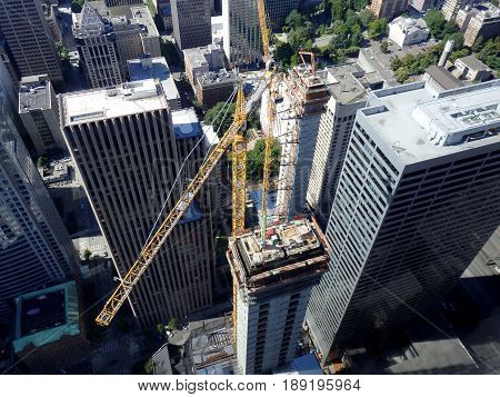 Aerial of Fifth + Columbia tower under construction with large cranes and surrounding towers in Seattle Washington.