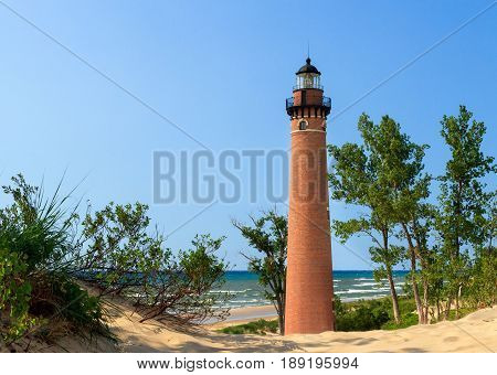 The natural red brick lighthouse at Michigan's Little Sable Point is viewed through sand dunes overlooking Lake Michigan surf.