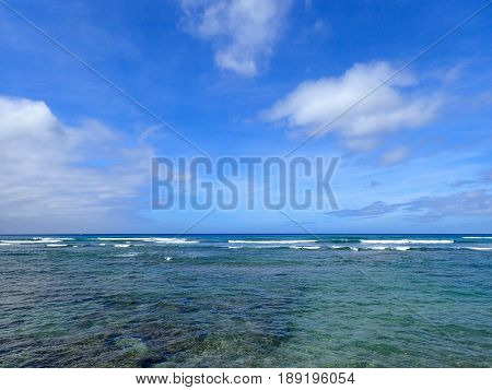 Shallow wavy ocean waters with coral beneath of Waikiki looking into the pacific ocean with a clear blue sky on Oahu.